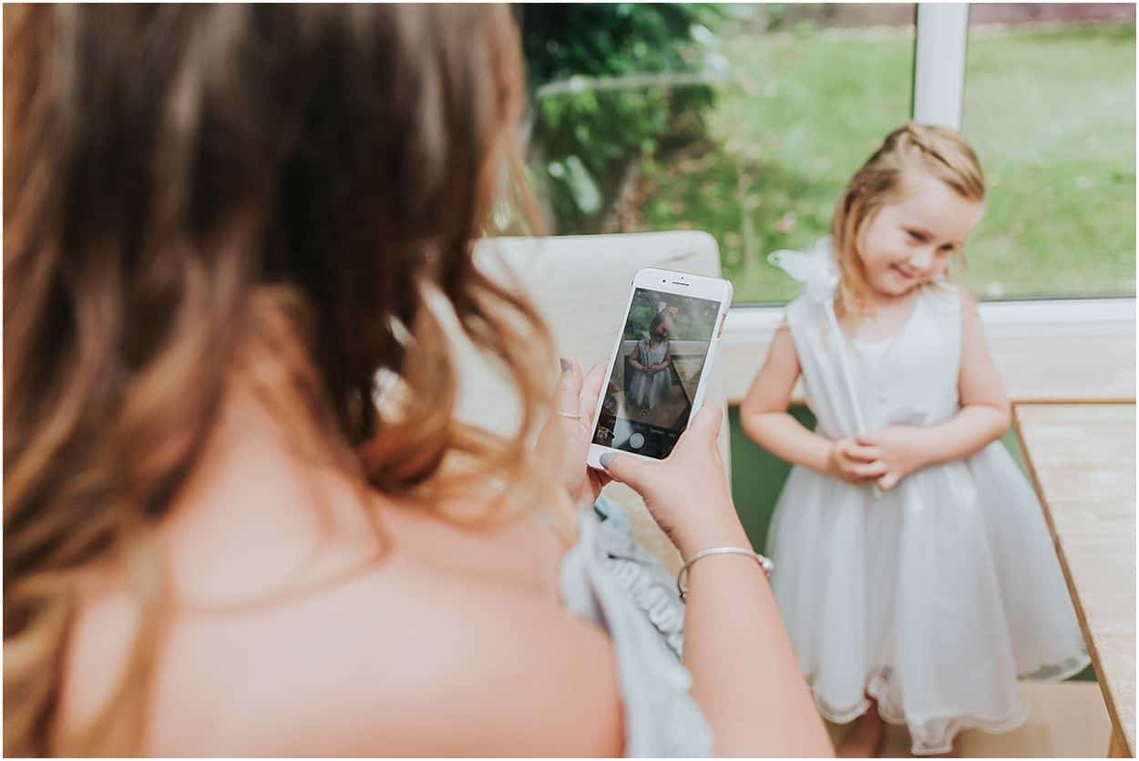Lincolnshire photography bridesmaid taking a picture of a flower girl