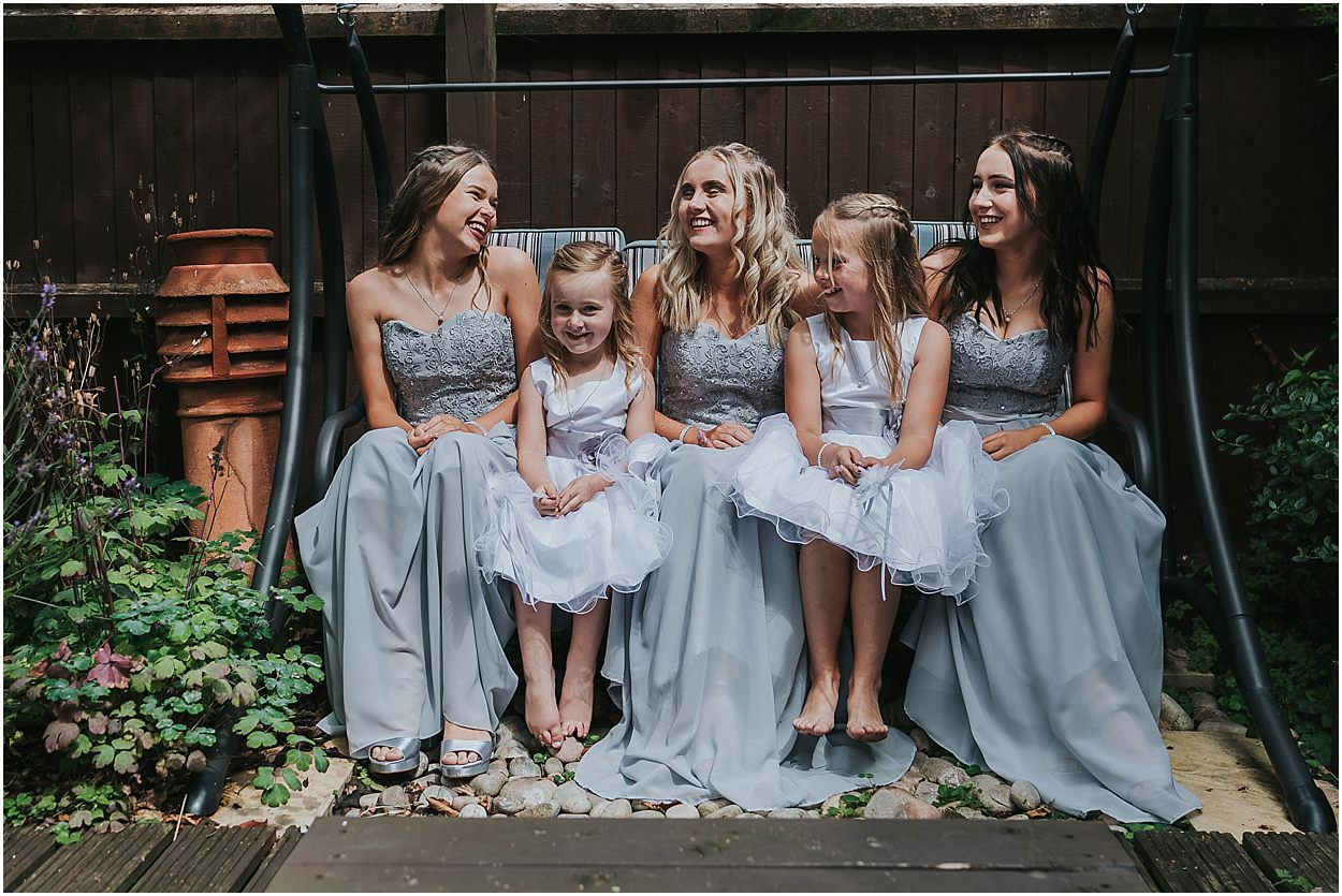 Lincolnshire photography bridesmaid and flower girls sitting on a garden swing laughing
