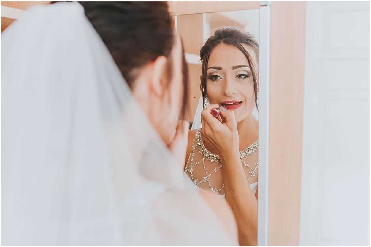 Lincolnshire photography bride applying lipstick in a mirror
