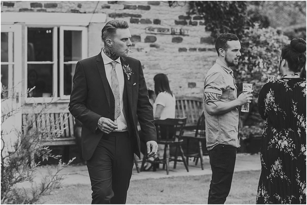 Lincolnshire photography groom walking across the venue courtyard smoking