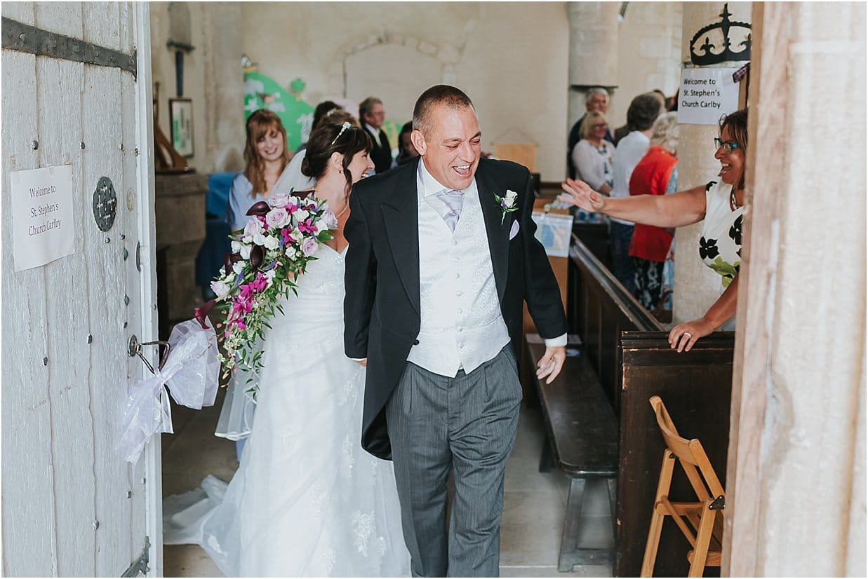 Rutland and Lincolnshire photography groom laughing as bride and groom leave the church
