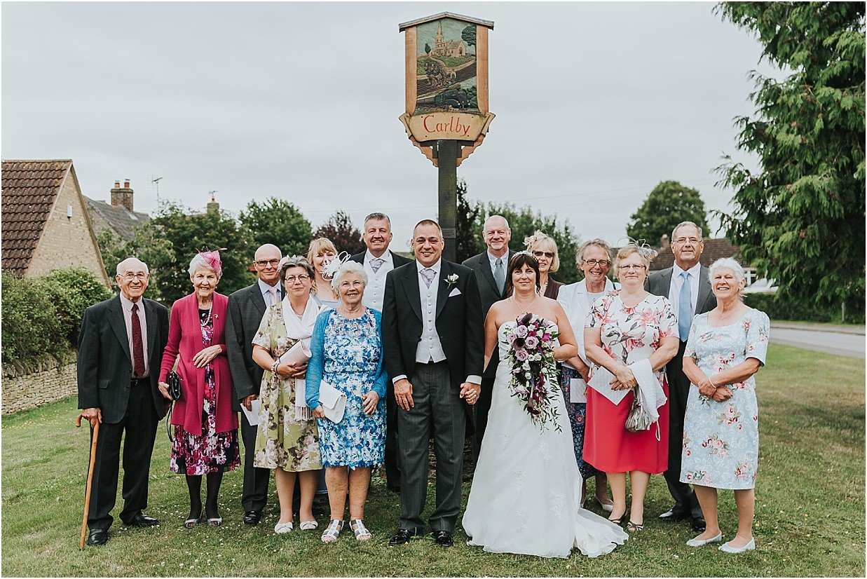 Rutland and Lincolnshire photography bride groom and carlby village residents outside the carlby village sign