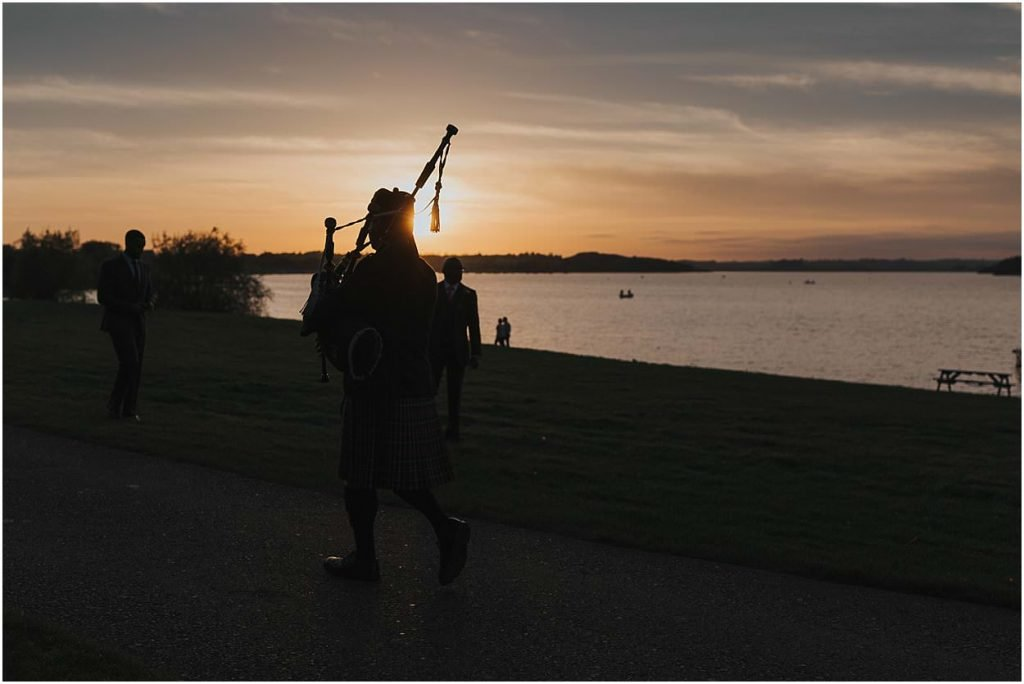Rutland weddings piper in front of a sunset over Rutland water Normanton church