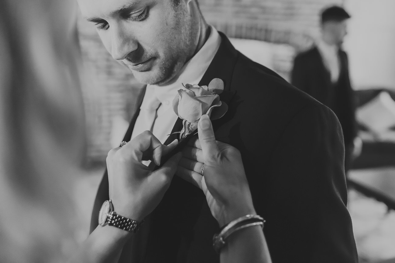 A groomsman having a button hole applied
