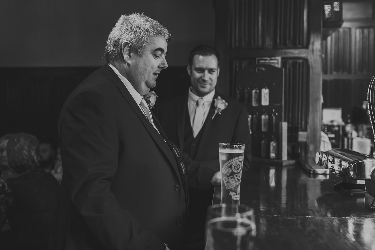Father of the groom enjoying a drink at the bar with a groomsman
