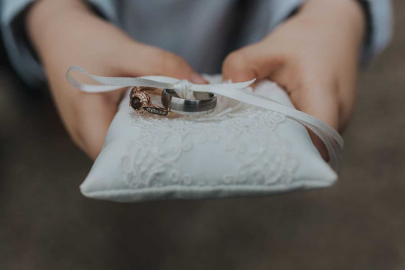 Page boy holding a cushion with the wedding rings on