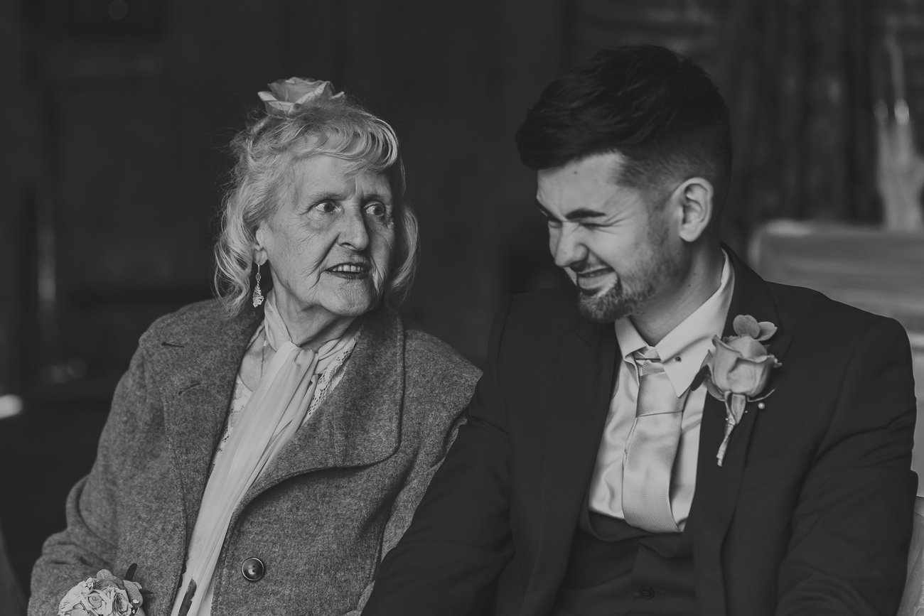 Best man being told a joke by his grandma