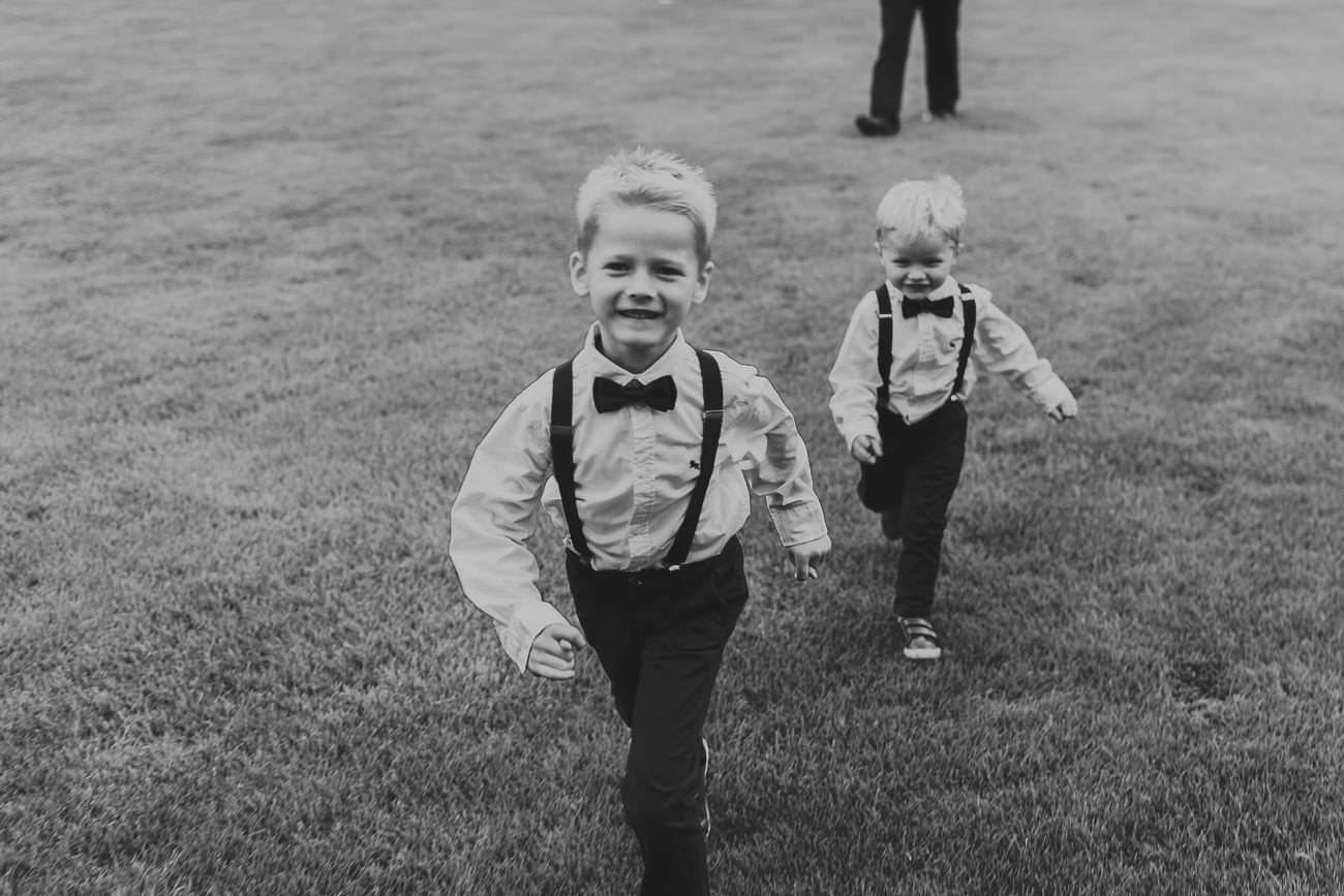 Two page boys running towards the camera at a wedding