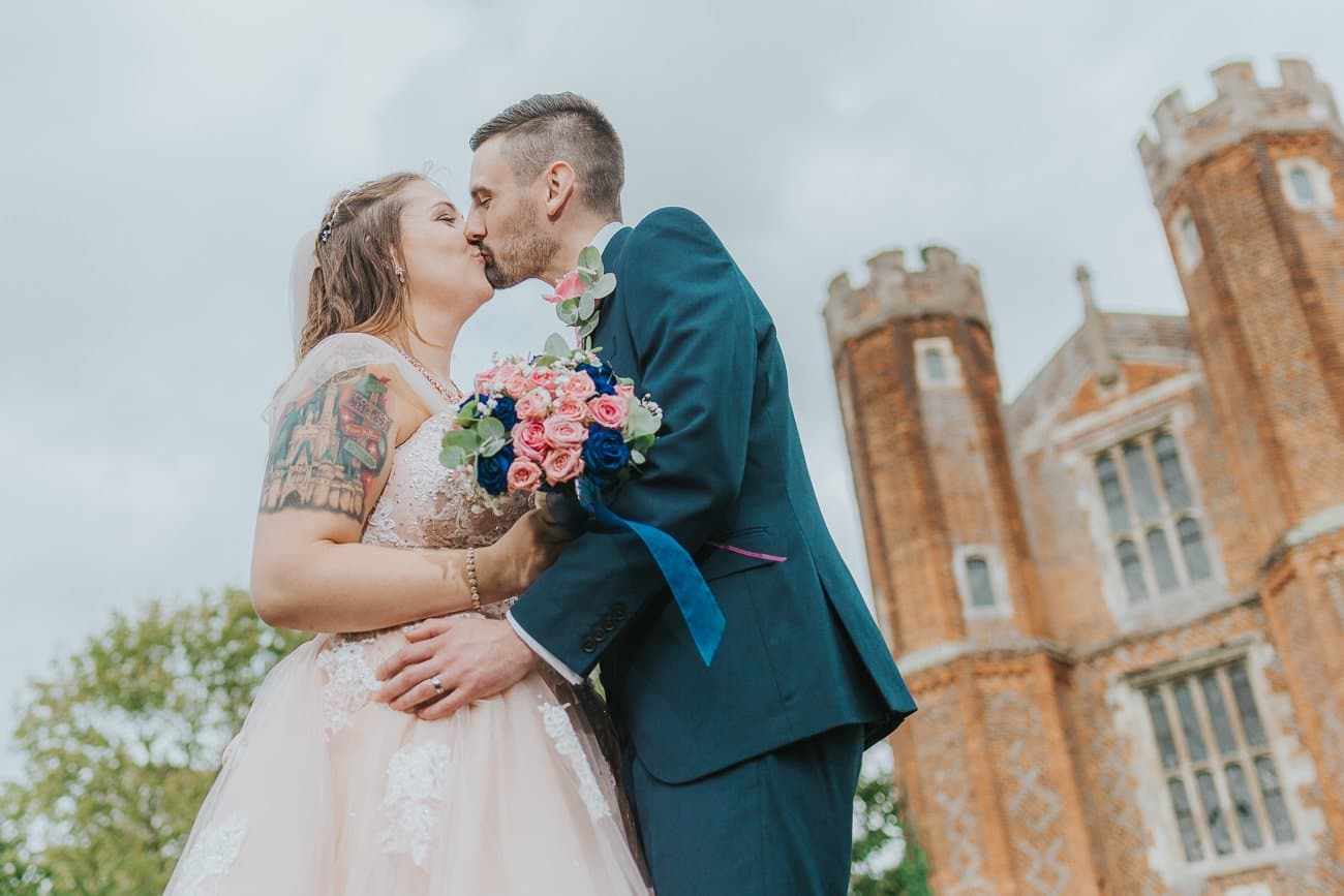 A bride and groom kissing in front of the tower at Leez Priory