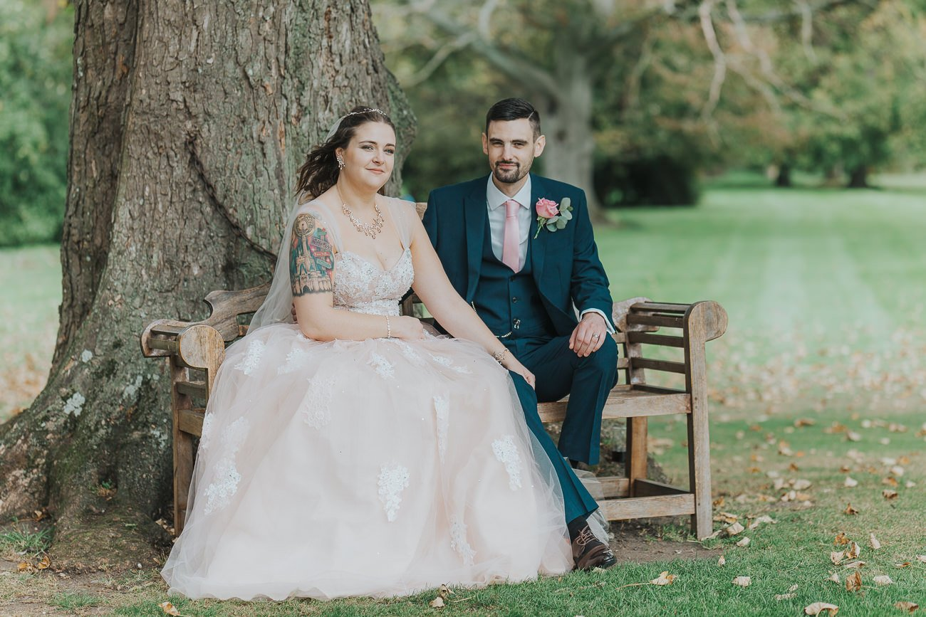 Bride and groom sat on a bench outside Leez Priory