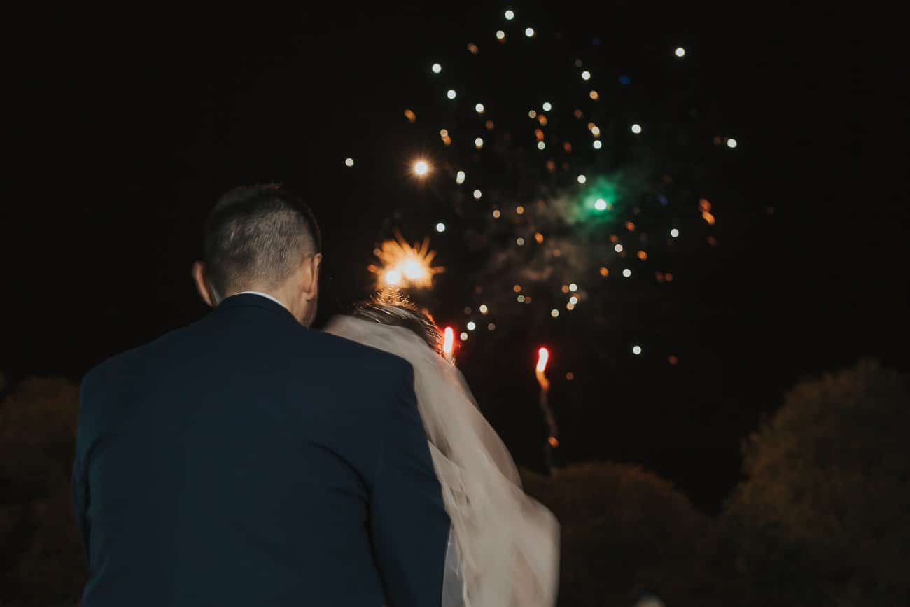 A bride and groom looking at fireworks after their wedding