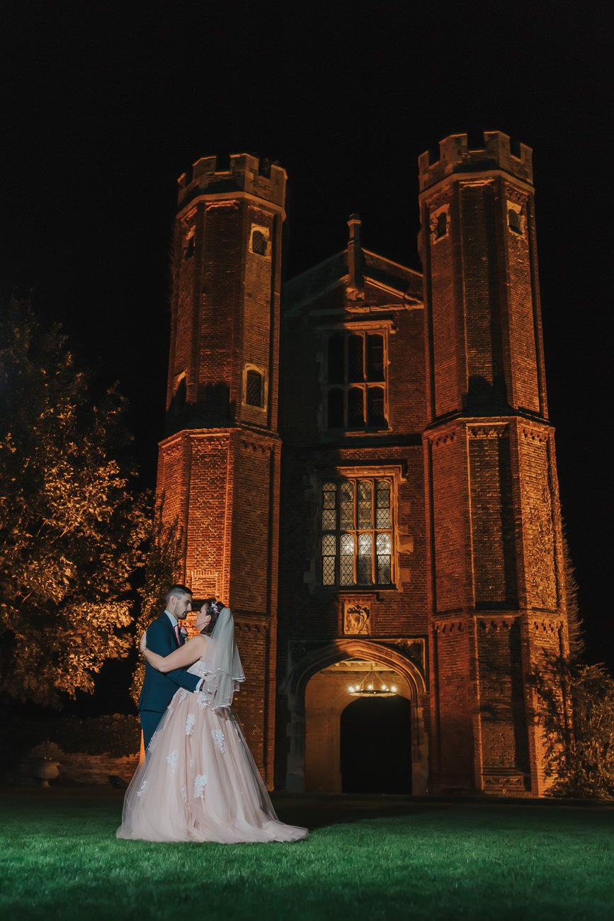 A bride and good in front of a tower at Leez Priory