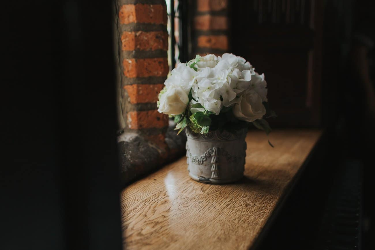 Small pot of white flowers on a windowsill at a wedding