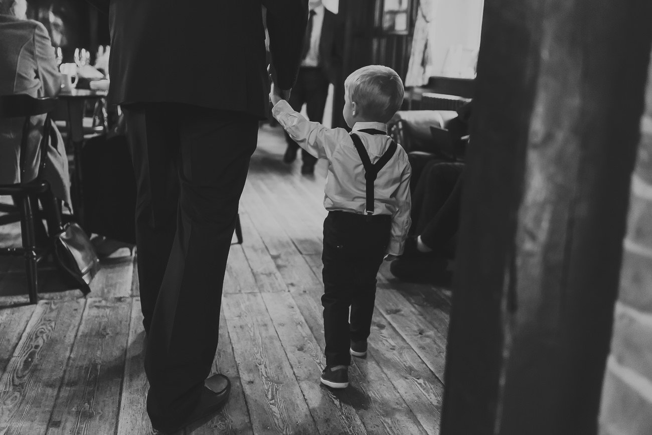 Page boy being led through a bar in black and white