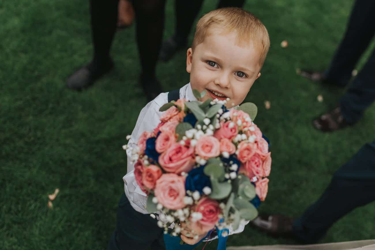 Bride's son holding her wedding bouquet