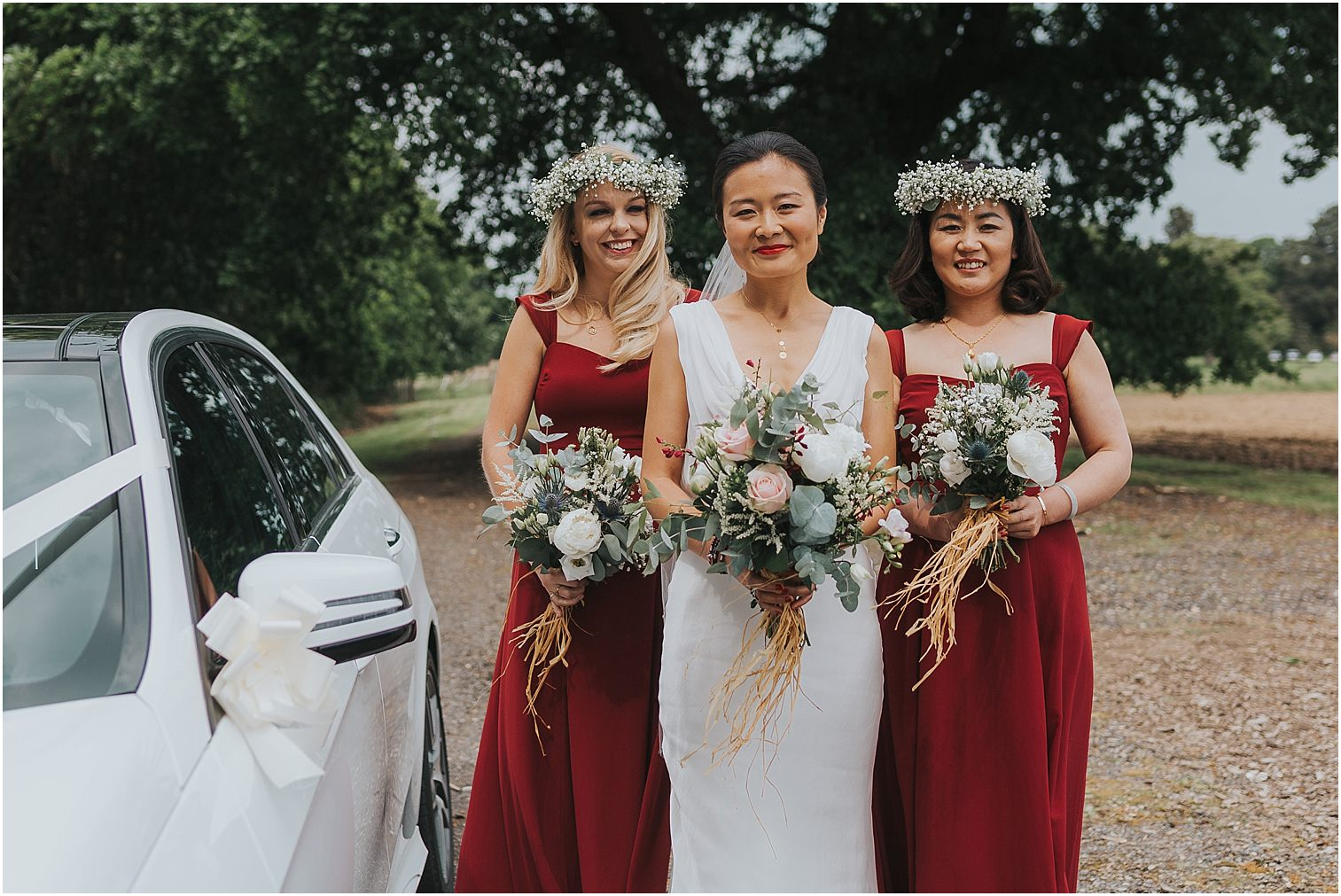 Bride with her bridesmaids standing next to their wedding car before getting married