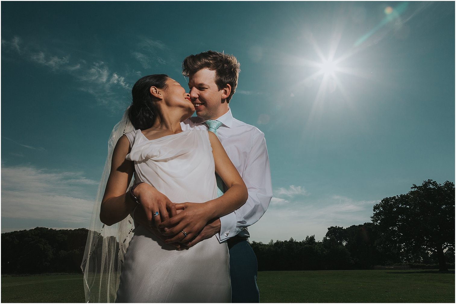 Bride and groom embracing with a sunburst behind them