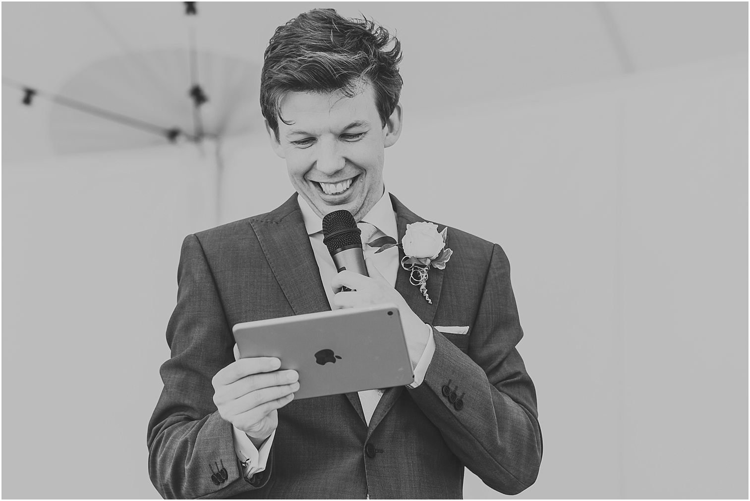 Black and white image of a groom reading his speech from an iPad