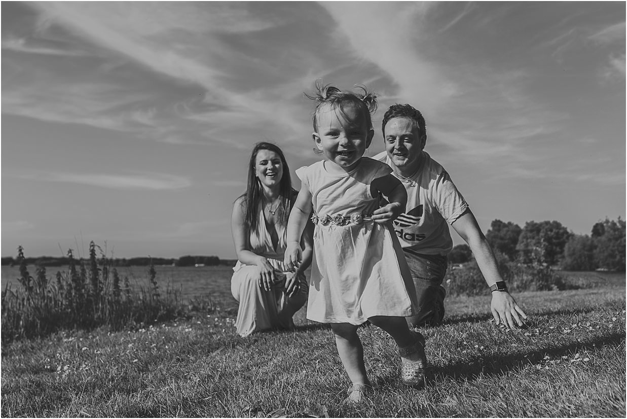Black and white image of a family chasing their daughter