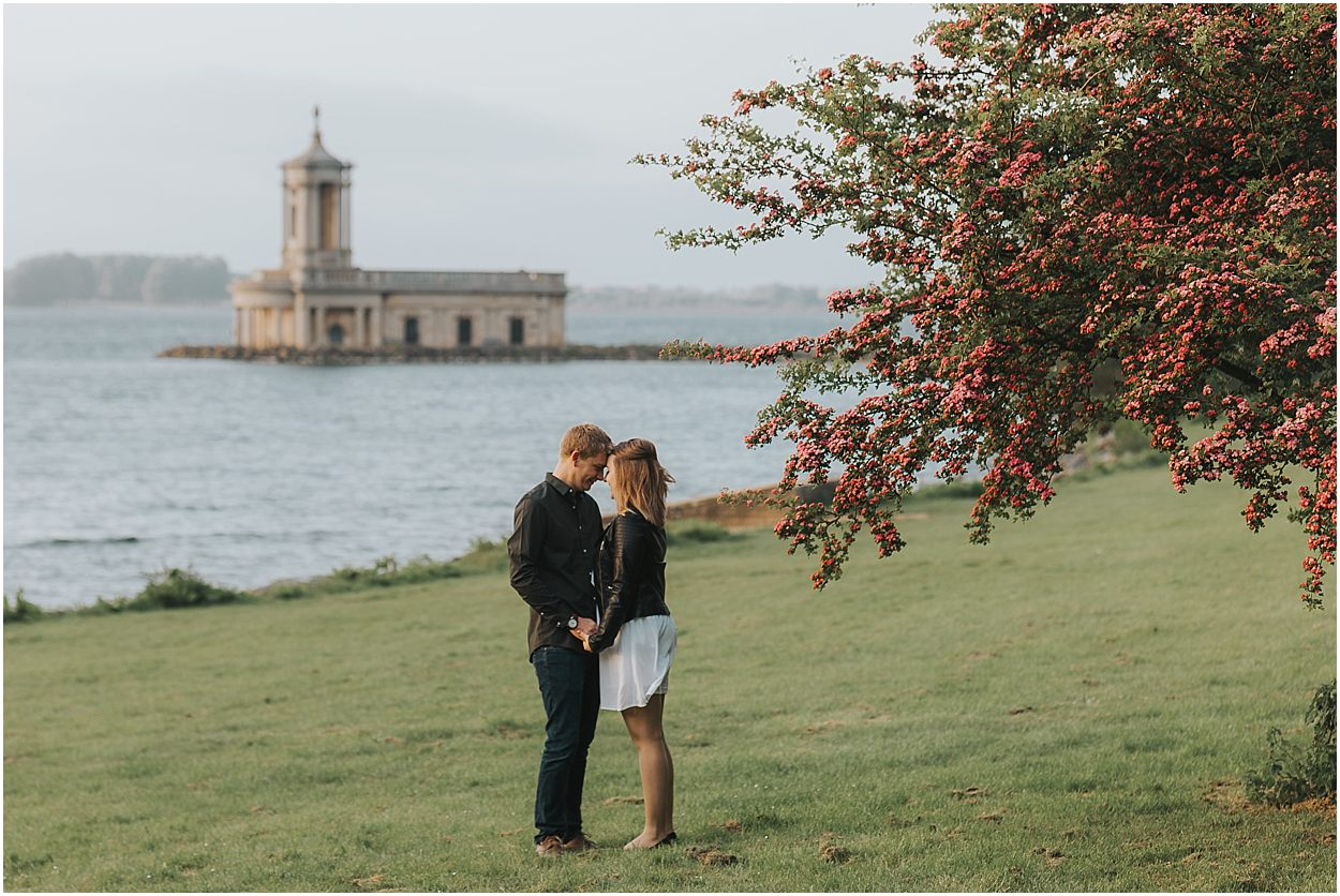 Rutland water engagement photography couple in front of Normanton church touching foreheads