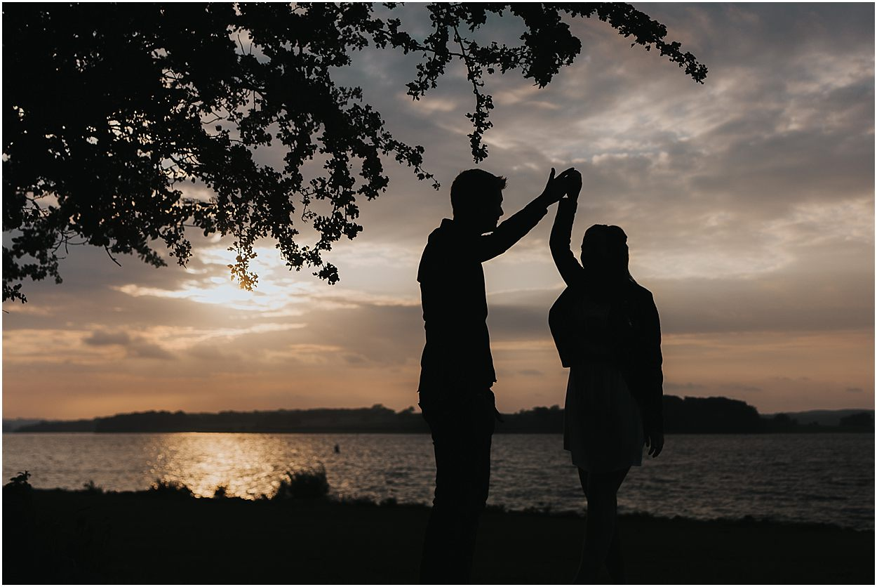 Rutland water engagement photography couple dancing on the shore of Rutland water