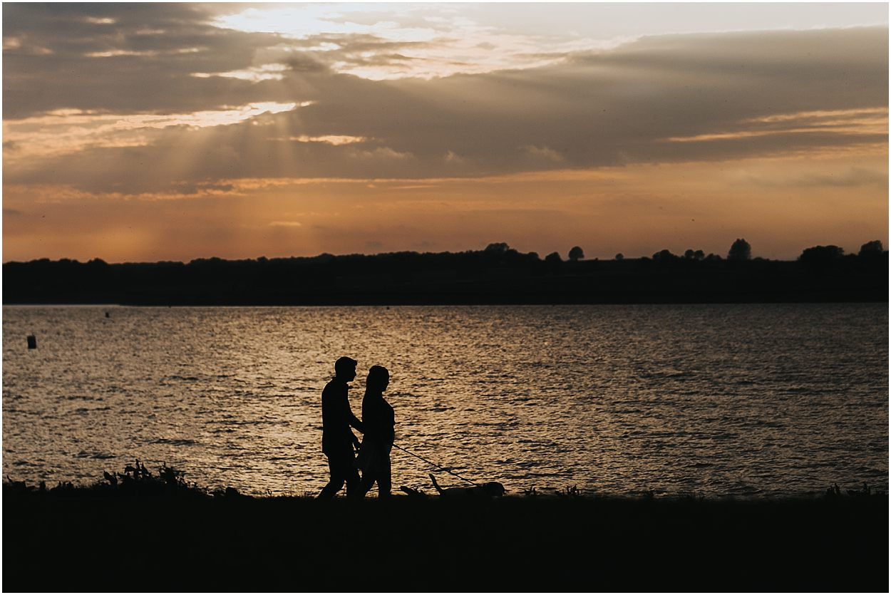 Rutland water engagement photography couple walking their dog along the shore of rutland water