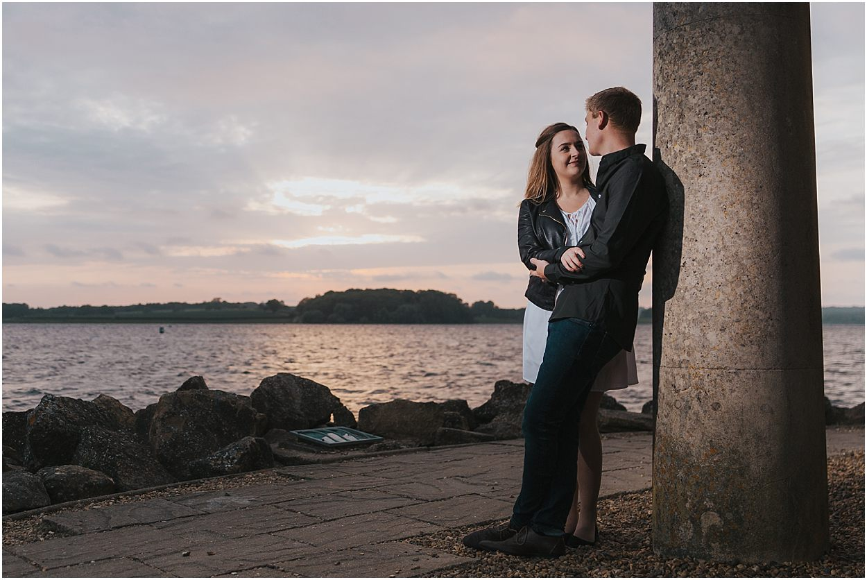Rutland water engagement photography Couple leaning on a pillar of Normanton church, rutland water