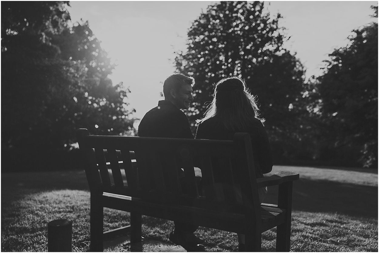 Rutland water engagement photography couple sat on a bench in love