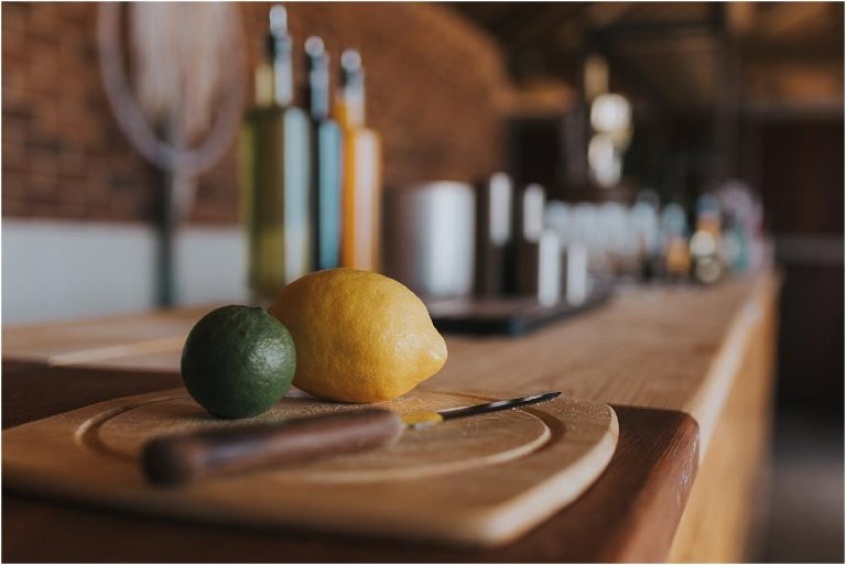 a lime and lemon on a chopping board on a bar