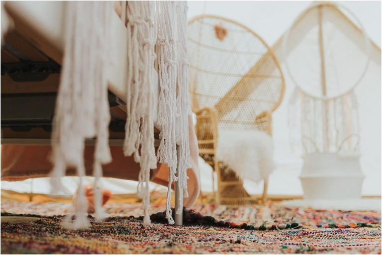 a tipi for a wedding dressed with lace and multicoloured rugs