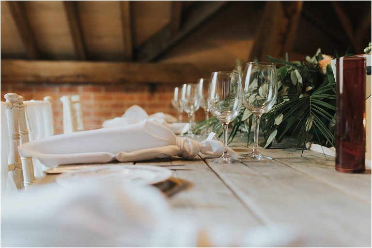 a rustic wedding table decorated with wine glasses and napkins