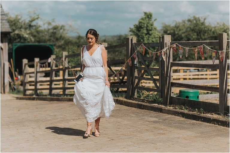 Northants wedding photographer a bride walking across a courtyard in a wedding dress