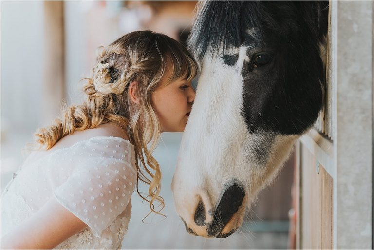 lady in a bridesmaid dress kissing a horse