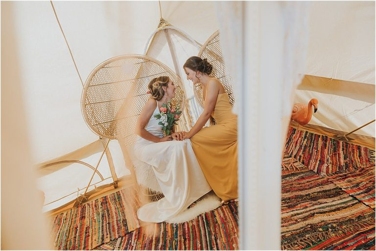 wedding photographer two ladies in a tipi laughing on their wedding day