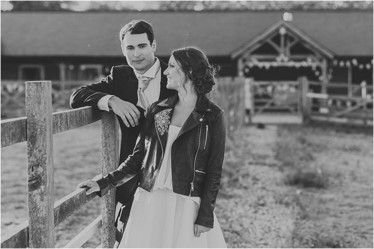 black and white image of a couple standing near a fence