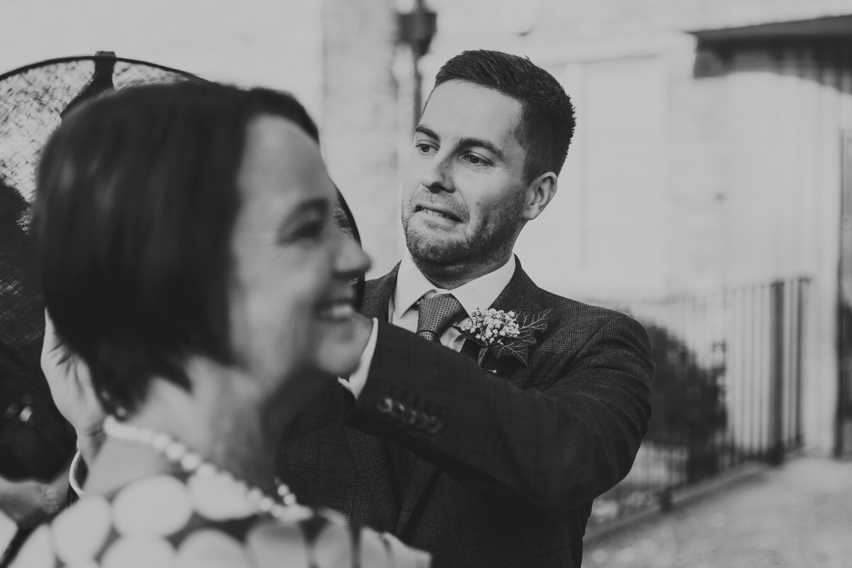 A groom rearranging a hat on a guest