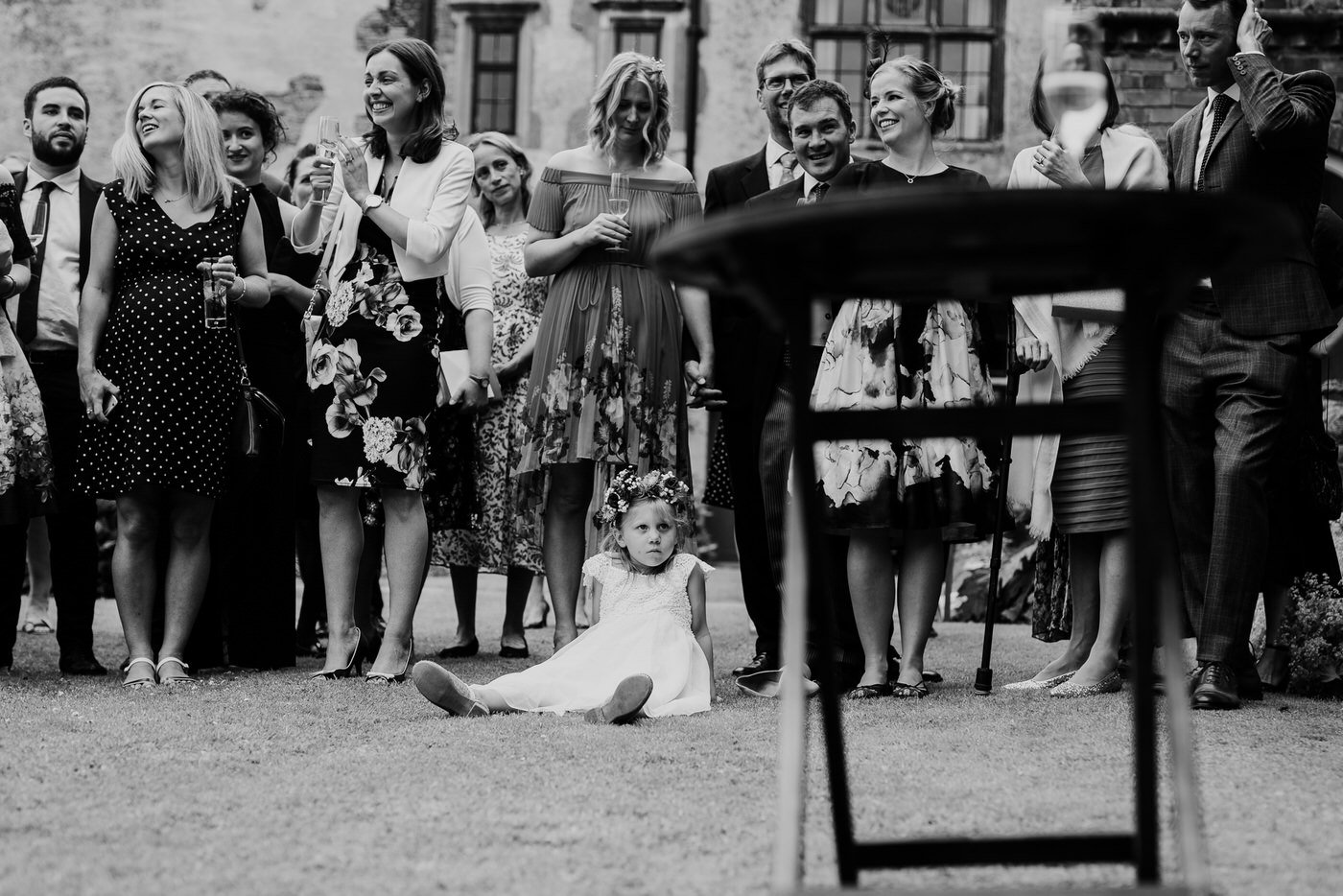 A flowegirl sitting on the floor while speeches take place