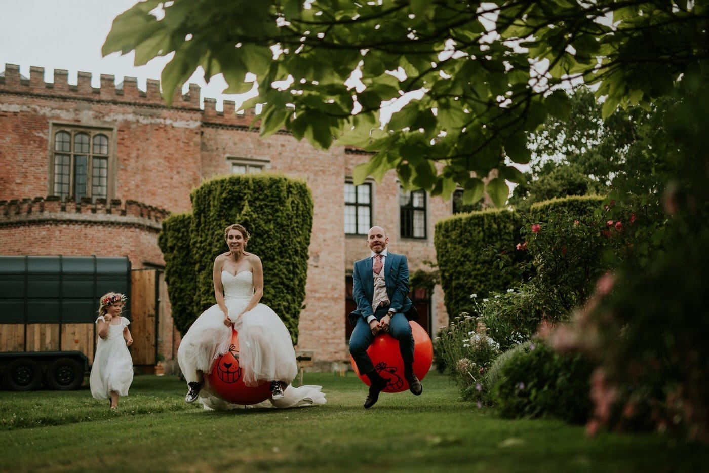 A bride and groom bouncing on space hoppers