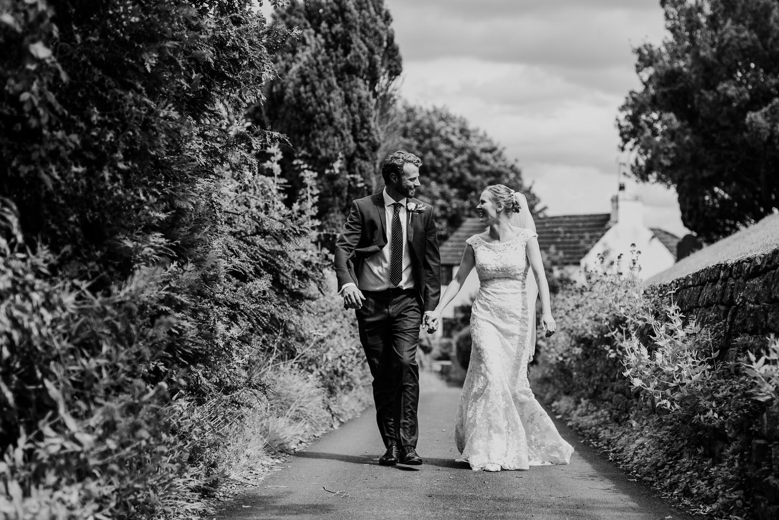 Bride and groom walking down a lane, in black and white