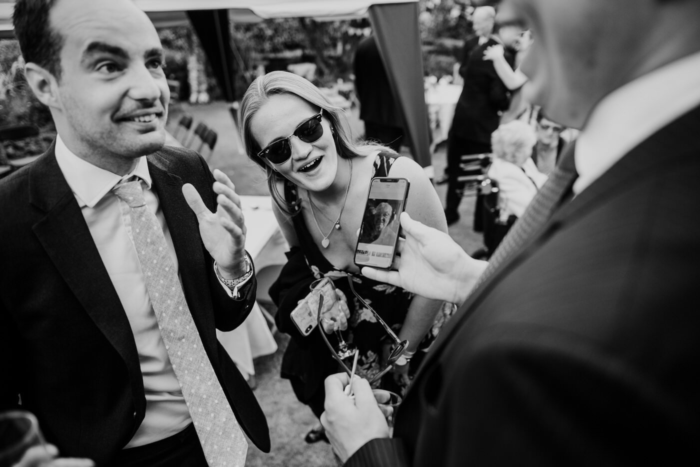 Wedding guests reacting to an image on a phone