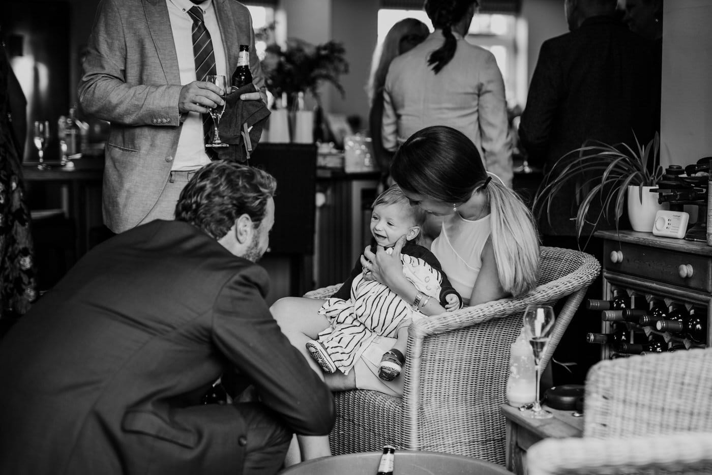A baby interacting with a groom at a wedding