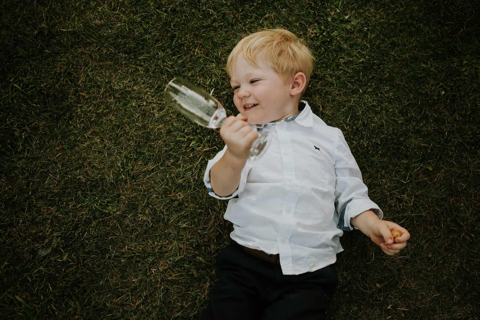 Child laying down holding a wine glass at a wedding reception