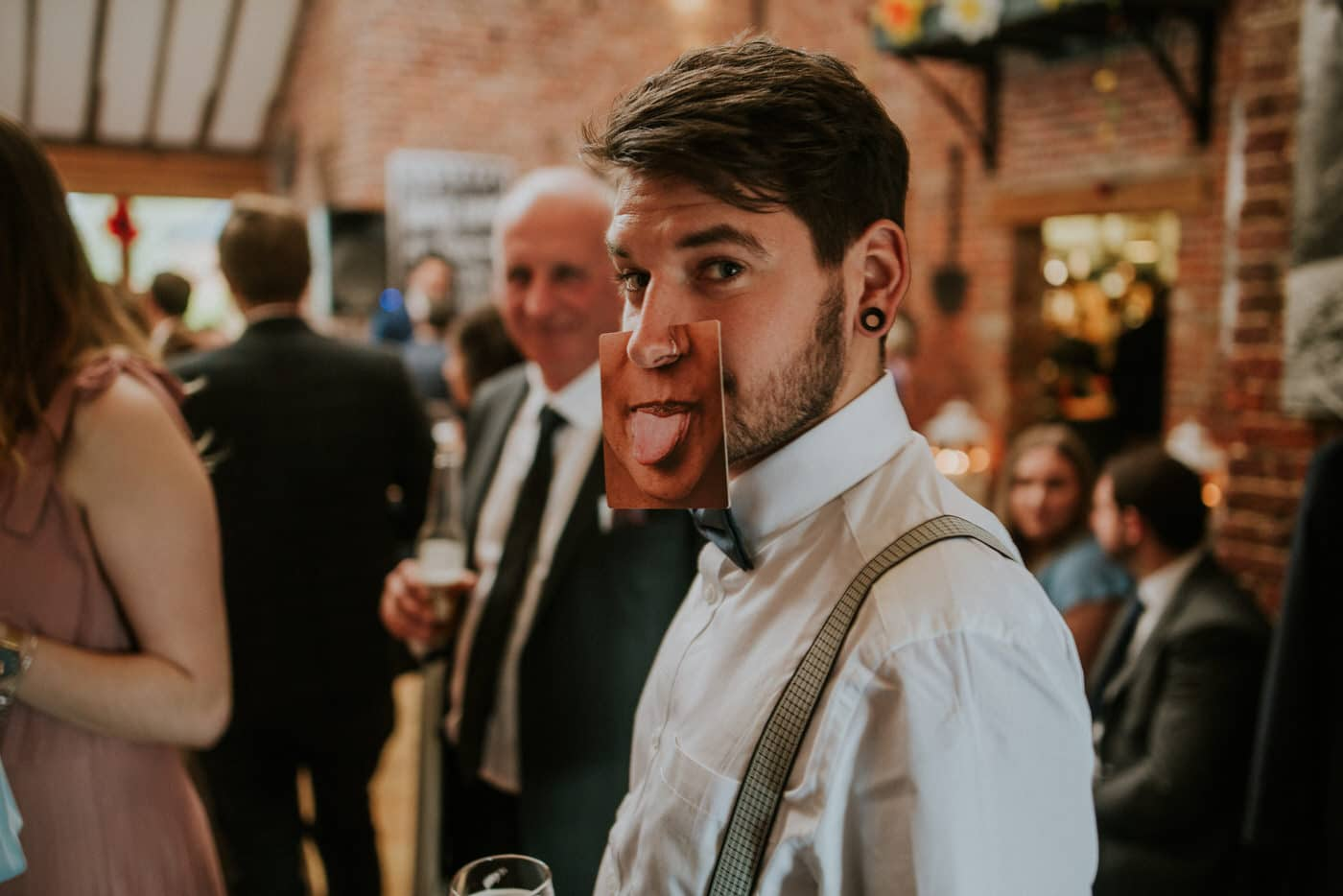 A man wearing a comedic mouth card at a wedding