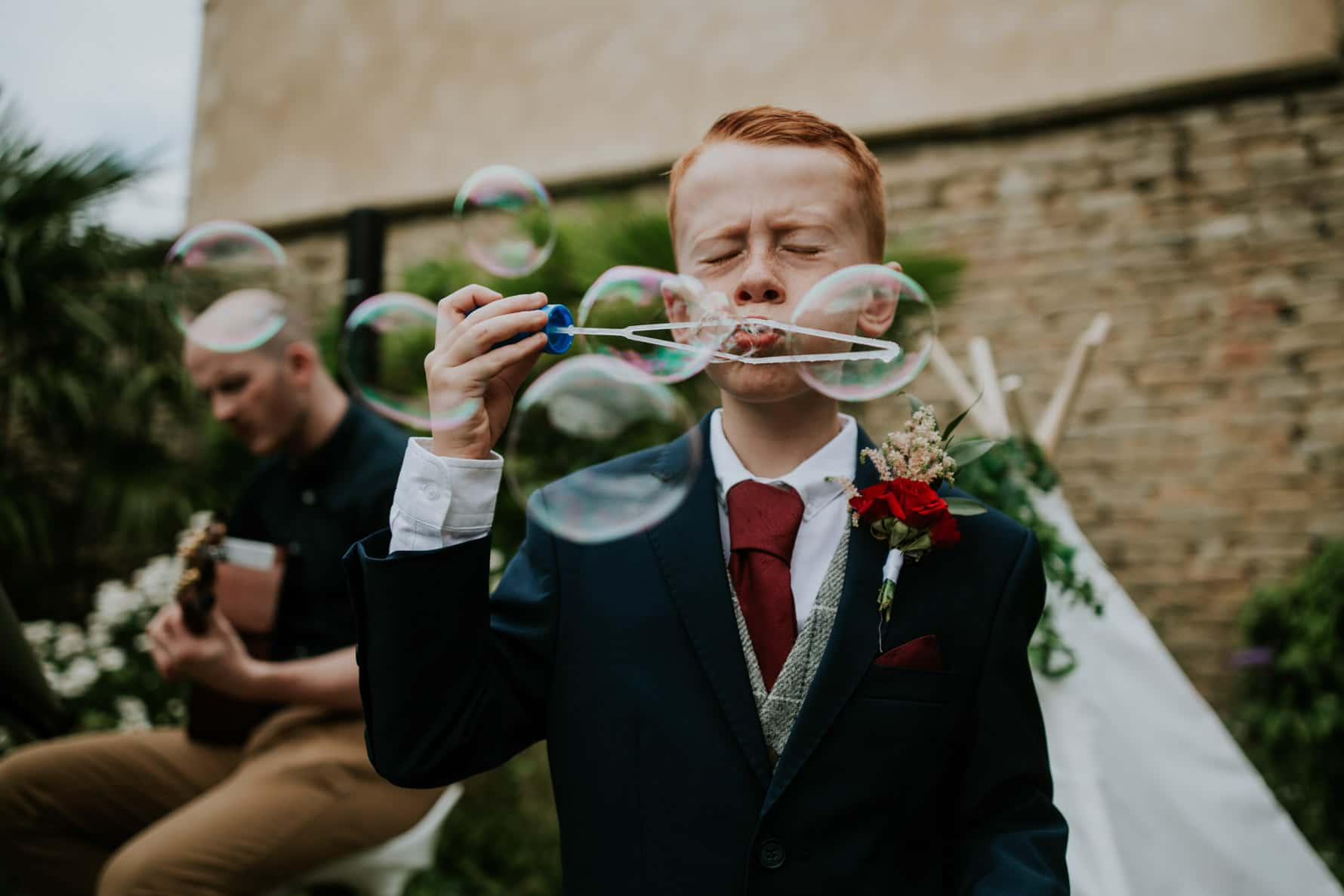 page boy blowing bubbles on a wedding day
