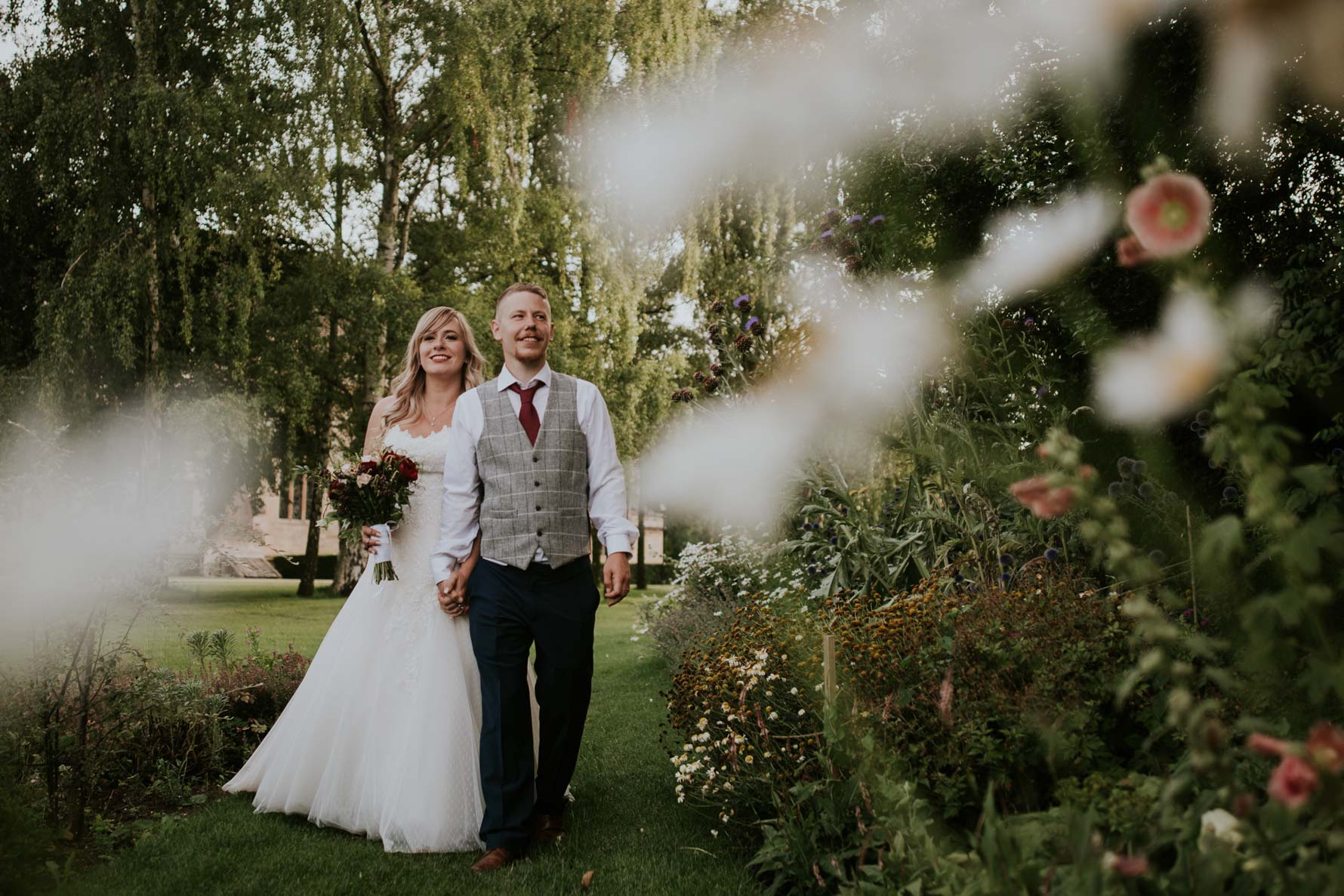 bride and groom walking through a garden - natural portraits