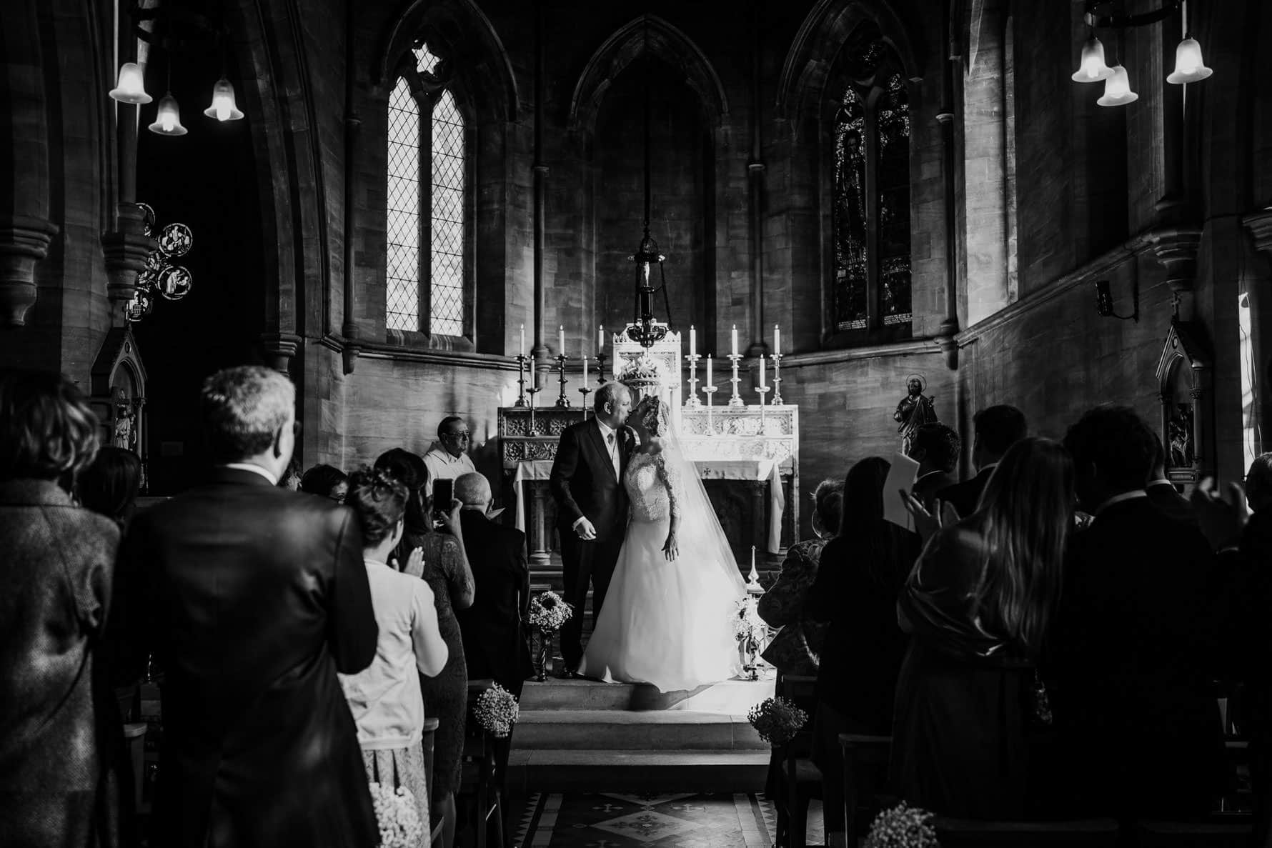 bride and groom kissing in a chapel
