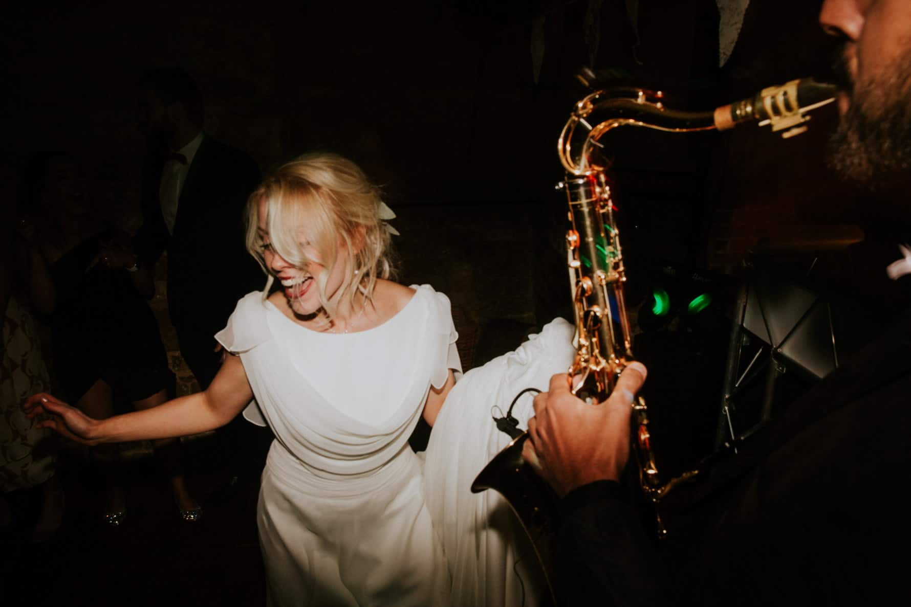 bride dancing with a saxophonist