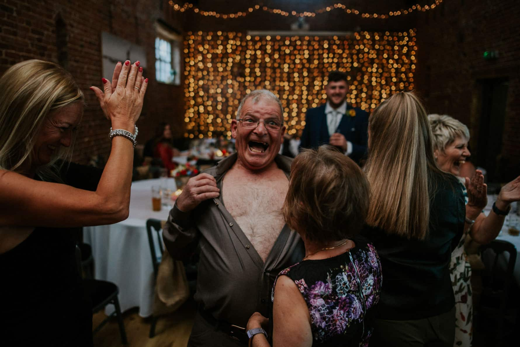 excited wedding guest ripping his shirt off