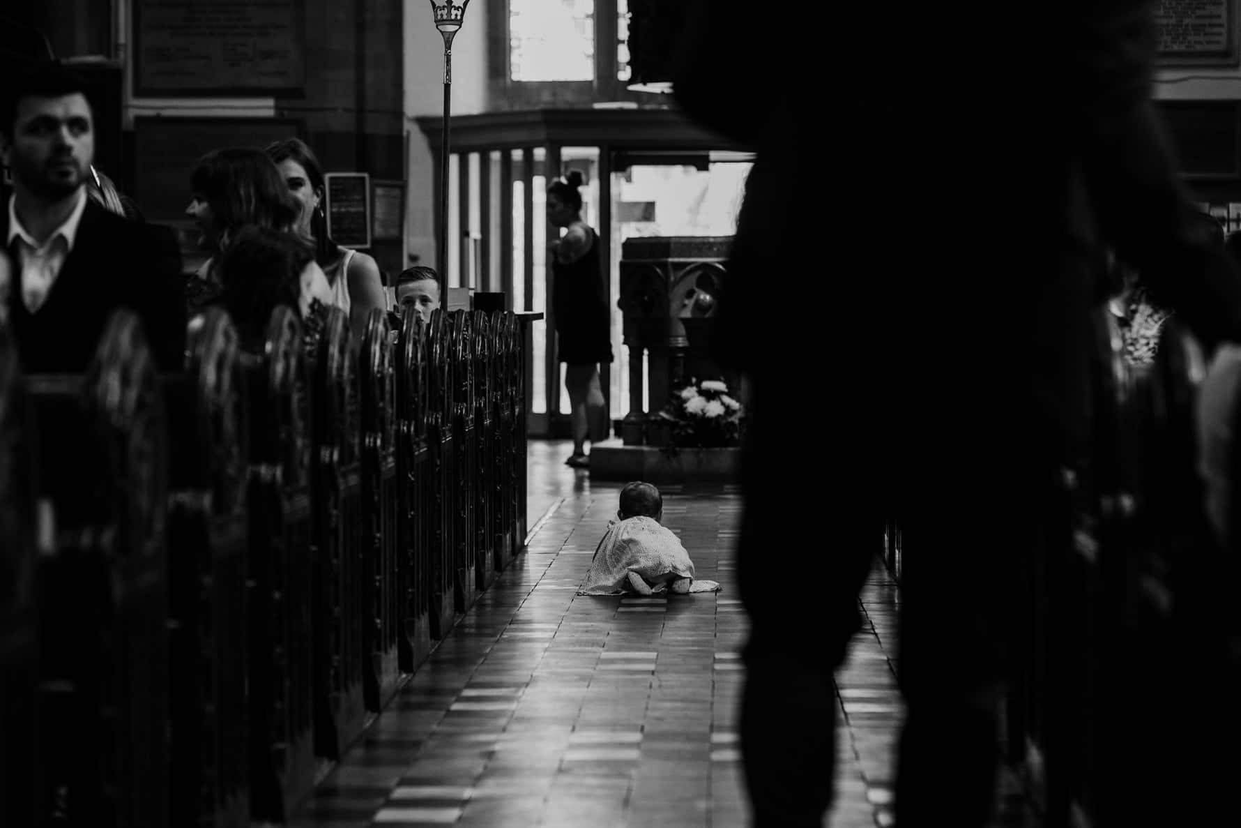 baby crawling down a church aisle