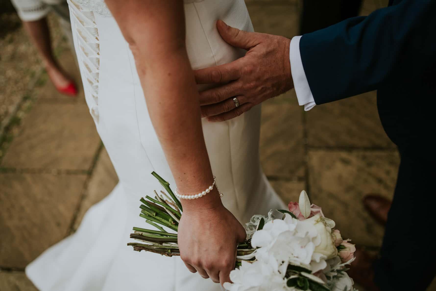 groom holding a bride's waist